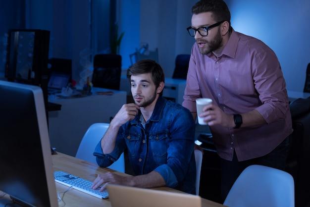 Comunicación con compañeros. programadores masculinos guapos inteligentes que miran la pantalla de la computadora y discuten un proyecto mientras trabajan juntos