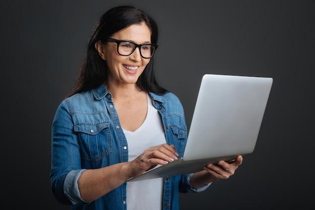Comunicación conveniente. mujer impresionante enfocada inteligente que usa su computadora portátil para escribir un correo electrónico y comunicarse con sus colegas mientras está de pie aislado sobre fondo gris