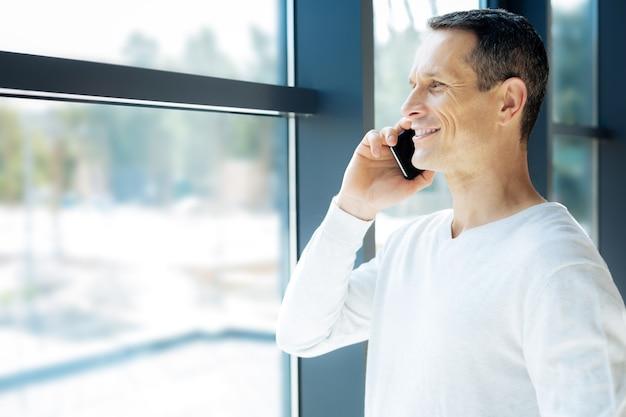 Comunicación a distancia. hombre guapo positivo alegre sonriendo y hablando con su amigo por teléfono mientras está de pie cerca de la ventana