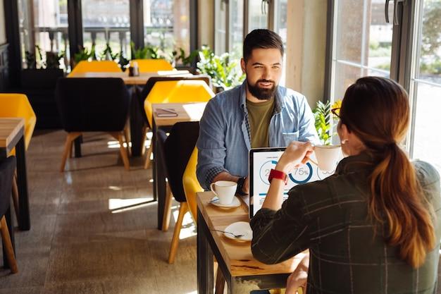 Comunicación laboral. buen hombre positivo hablando con su colega mientras visitaba una cafetería con él