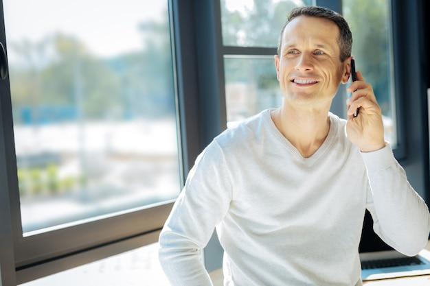 Comunicación móvil. hombre atractivo encantado alegre poniendo un teléfono en la oreja y sonriendo mientras escucha a su interlocutor