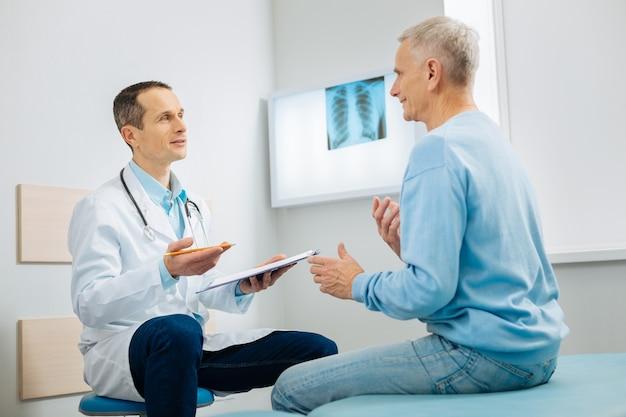 Comunicación profesional. médico alegre positivo y paciente sentados uno frente al otro y hablando mientras discuten los síntomas
