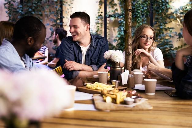 Comunicándose con colegas multiculturales en el pequeño y acogedor restaurante local con deliciosa comida.