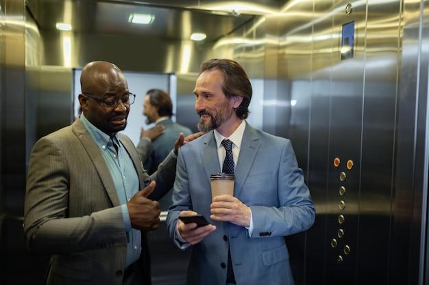 Comunicarse con el colega. empresario de pelo gris sonriendo mientras se comunica con su colega en el ascensor