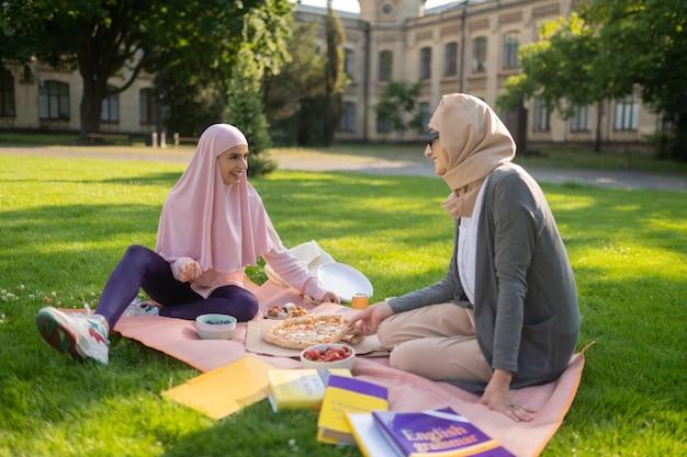 Comunicarse y comer. estudiantes musulmanes alegres que se comunican y almuerzan afuera
