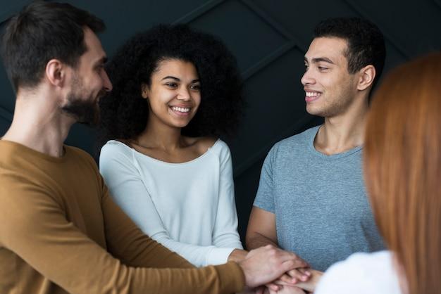 Comunidad de jóvenes positivos tomados de la mano