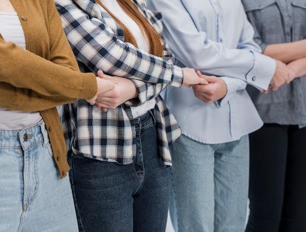 Comunidad de mujeres juntas cogidas de la mano