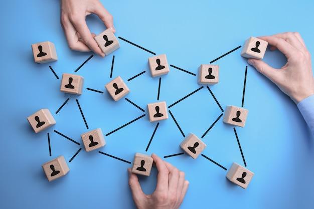 Comunidad de red: las manos del hombre ponen los ladrillos de madera con el icono de persona