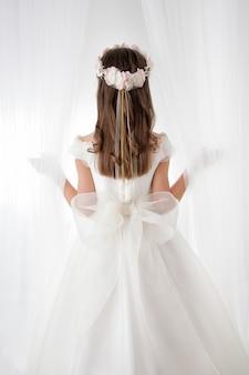 Comunión niña de espaldas entre dos cortinas blancas