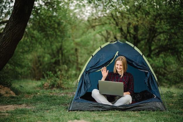 Comuníquese con familiares, familiares en línea en una computadora portátil en una carpa en la naturaleza