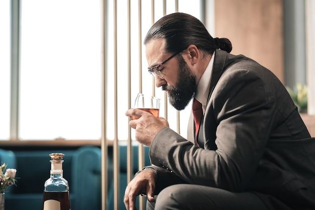 Coñac de calidad. hombre moreno barbudo con gafas oliendo coñac de calidad cara