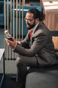 Coñac caro. empresario barbudo sosteniendo una botella de coñac caro que se le presentó después de la reunión
