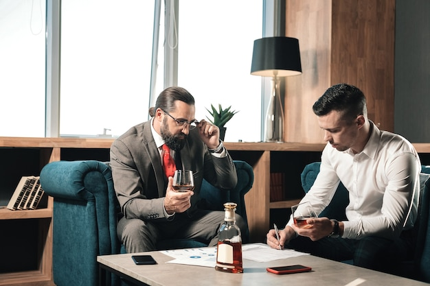Coñac en la oficina. dos socios comerciales exitosos inteligentes sentados a la mesa en la oficina y bebiendo coñac