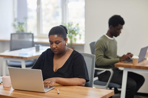 Concentarted emprendedora que trabaja en la computadora portátil que está leyendo un artículo o informe en línea