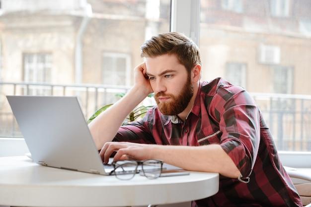 Concentrado barbudo joven usando la computadora portátil.