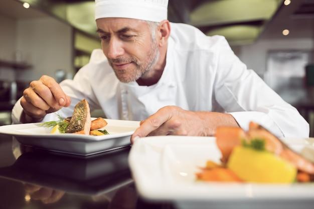 Concentrado chef masculino guarnición de comida en la cocina