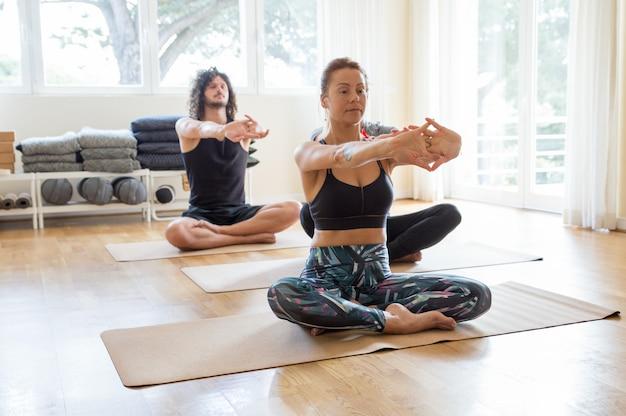 Concentrado chico y chica haciendo yoga en el gimnasio