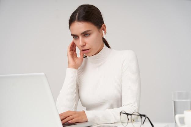 Concentrado joven bastante mujer de cabello oscuro con auriculares mientras está sentado sobre una pared blanca, mirando atentamente la pantalla de su computadora portátil mientras trabaja en la oficina