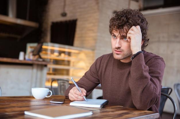 Concentrado pensativo guapo joven pensativo rizado en sweetshirt marrón escribiendo en el cuaderno sentado en la cafetería y bebiendo té