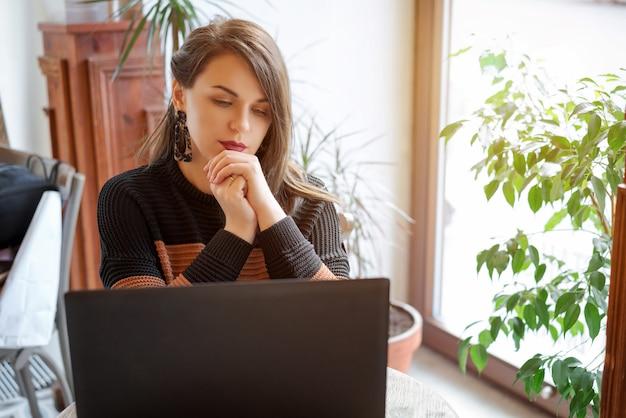 Concentrado en el trabajo. mujer joven confiada en la ropa de sport elegante que trabaja en el ordenador portátil mientras que se sienta cerca de ventana o del café.