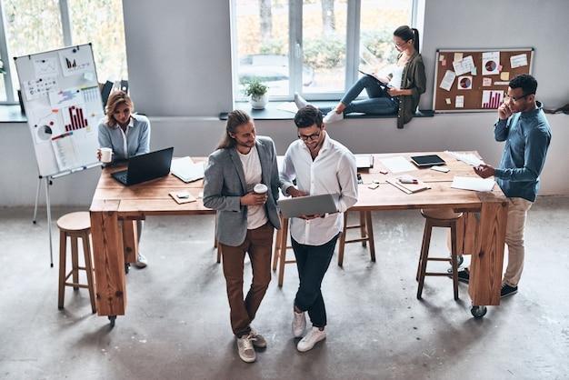Concentrado en el trabajo. vista superior de los jóvenes modernos que trabajan juntos mientras pasan tiempo en la oficina