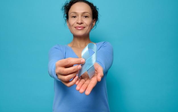 Concéntrese en la cinta de raso azul, color del arco simbólico del día mundial de la concienciación sobre la diabetes, en manos de una hermosa mujer de raza mixta con una sudadera azul, aislada sobre fondo de color con espacio de copia