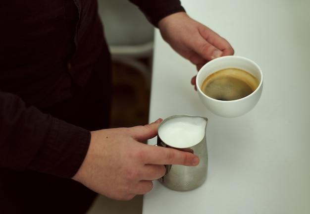 Concéntrese en las manos de los baristas que sostienen en una mano una taza de café y en la otra leche