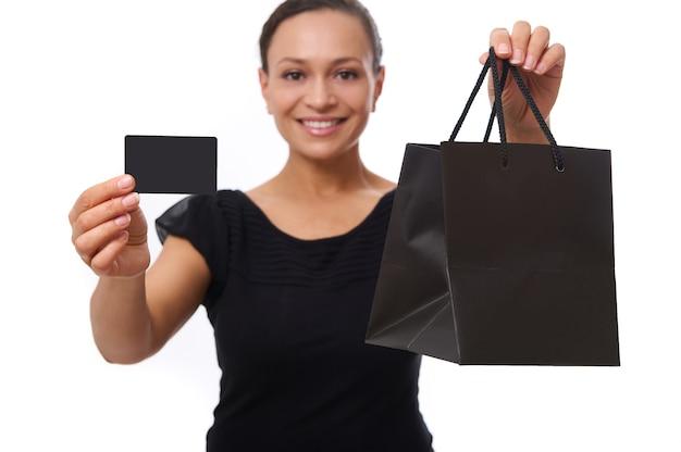 Concéntrese en la tarjeta de crédito o descuento de plástico y la bolsa de compras negra en las manos de fuera de foco hermosa mujer sonriente con una gran sonrisa, aislada sobre fondo blanco con espacio de copia. viernes negro