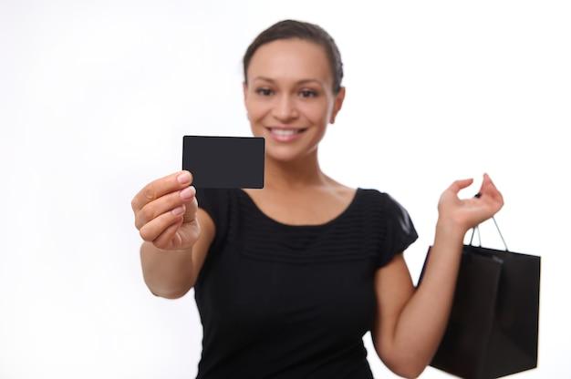 Concéntrese en la tarjeta de descuento de crédito de plástico negro en blanco con espacio de copia en la mano extendida de la hermosa mujer sonriente vestida de negro y sosteniendo el bolso de compras, aislado sobre fondo blanco. viernes negro