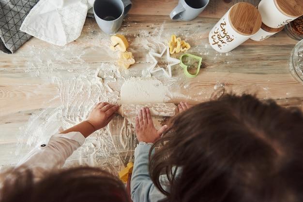 Concepción de la cocina. vista superior de niños que aprenden a preparar la comida de la harina con instrumentos especiales formados