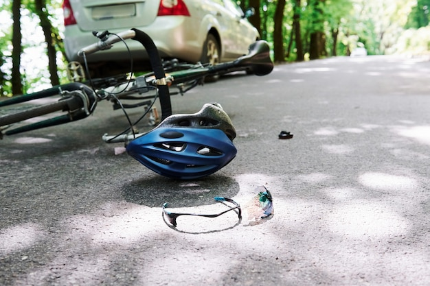Concepción de descuido. bicicleta y accidente de coche de color plateado en la carretera en el bosque durante el día