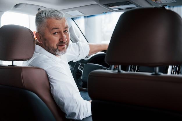 Concepción del éxito. hombre barbudo alegre en camisa blanca mira hacia atrás mientras está sentado en el automóvil moderno