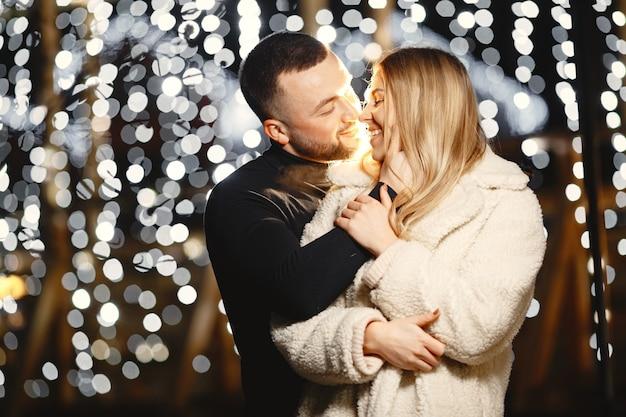 Concepción de las vacaciones de invierno. retrato nocturno al aire libre de una pareja joven. posando en la calle de la ciudad europea.