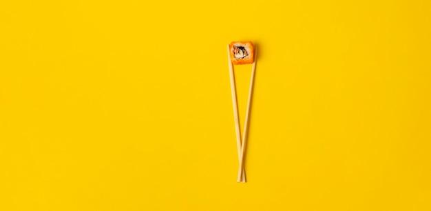Un concepto abstracto de los palillos de madera asiáticos con un rollo de comida nacional en la superficie de color, pancarta ancha