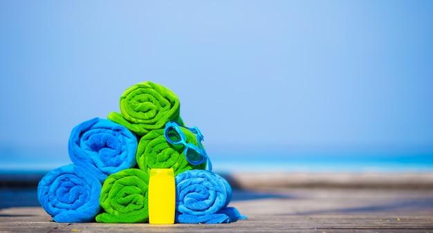 Concepto de accesorios de playa y vacaciones de verano: primer plano de toallas de colores, gafas de natación y protector solar
