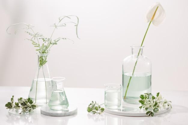 Concepto de aceites de perfume. cristalería de laboratorio con agua floral infundida en mesa