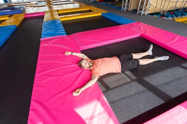 Concepto de actividad fitness, diversión, ocio y deporte - hombre acostado en un trampolín en el interior, vista superior