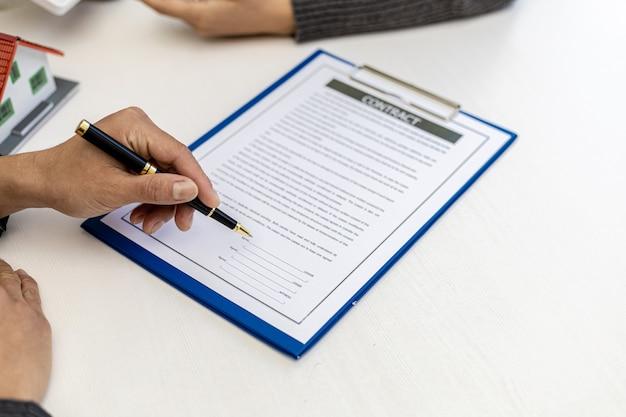 Concepto de acuerdo de contrato inmobiliario. el comprador está firmando el contrato de compra de la casa con el vendedor. el vendedor calcula el costo de compra de la casa y explica los detalles del contrato.