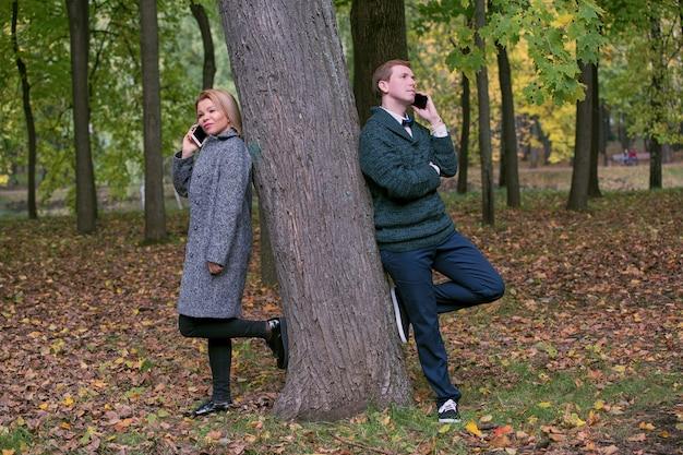 Concepto de adicción al teléfono móvil: pareja usando su teléfono móvil en una cita al aire libre