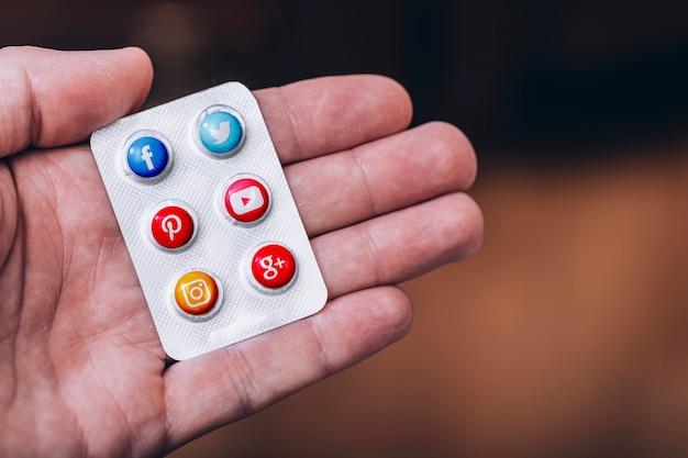 Concepto de adicción a la red social, píldoras con el logotipo de las redes sociales más famosas