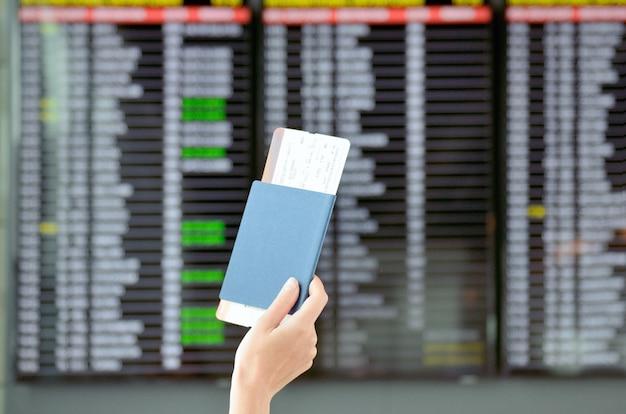 Concepto de aeropuerto y viaje, mano con pasaporte y billetes de avión con fondo de horario en terminal