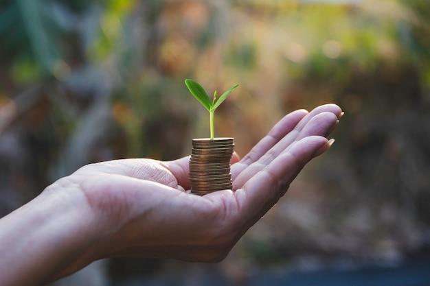Concepto de ahorro de dinero con la mano que sostiene el dinero pila de monedas.