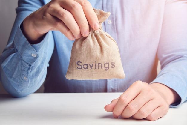 Concepto de ahorro. el hombre sostiene una bolsa de dinero.