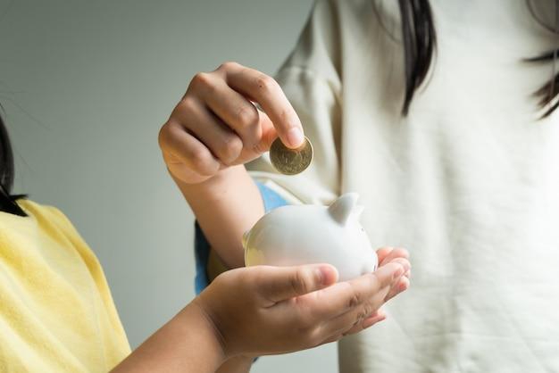 Concepto de ahorro y negocios, dos niña con hucha y monedas en casa