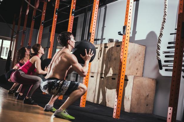 Concepto de ajuste, deporte y ejercicio: personas con balones medicinales entrenando en el gimnasio
