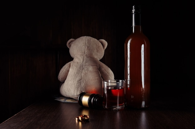Concepto de alcohol y divorcio. oso de peluche, anillos y botella con vidrio en una habitación oscura.