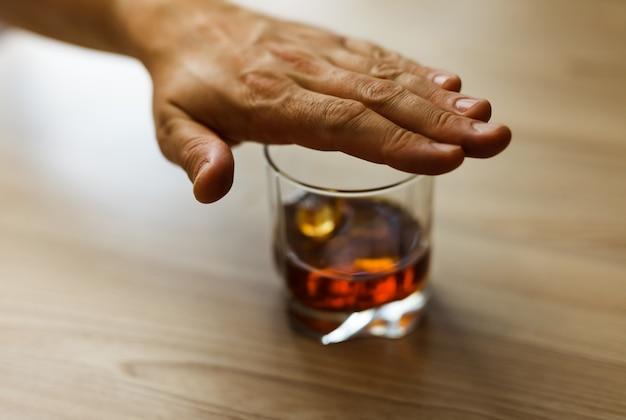 Concepto de alcoholismo. las manos bloquean la cadena de un vaso de whisky