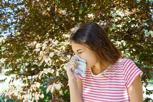 Concepto de alergia. chica joven que estornuda con el limpiador de la nariz entre árboles florecientes en parque