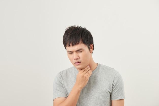 Concepto de alergias y dolor de garganta. joven enfermo sobre fondo blanco.