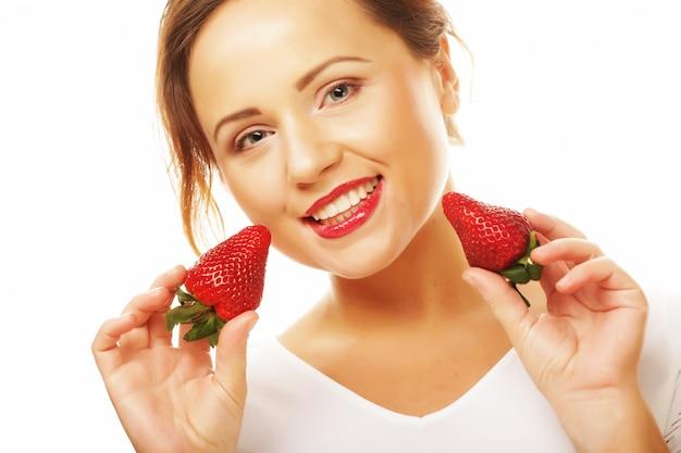 Concepto de alimentación, alimentación y dieta saludable - joven hermosa mujer sonriente feliz con fresa